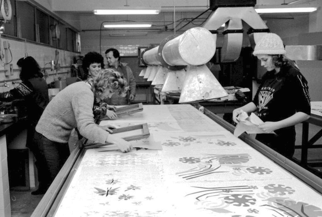 Audiodescrição da imagem: Fotografia horizontal, em preto e branco, de quatro mulheres e um homem trabalhando com tecidos em um laboratório têxtil. Em primeiro plano, o tampo de uma bancada retangular, que vai até o centro do ambiente. Sobre este, algumas estampas impressas em um tecido longo e único, de figuras geométricas, de borboletas, de flores, entre outras. Estas estampas são recortadas por mulheres que manejam instrumentos quadrados de madeira, como a moldura de um quadro, para a medição do recorte. São três mulheres ao redor da bancada retangular: duas na lateral esquerda, uma ao lado da outra, e uma na lateral direita. A primeira, à esquerda, enquadrada do joelho para cima, de perfil direito e inclinada sobre a bancada, manuseia com a mão esquerda um instrumento de medição enquanto segura o tecido com a mão direita, concentrada na ação. Ela é magra, com traços finos, o cabelo claro, curto e bastante ondulado, veste um suéter claro e calça escura. A mulher ao lado, enquadrada da cintura para cima, sorri e olha para a ação da primeira mulher, enquanto também segura um dos instrumentos de medição. Ela está parcialmente oculta pela primeira mulher, é magra, com rosto oval, tem o cabelo curto e crespo, em tom escuro, e, da sua vestimenta, vê-se somente as mangas. E a mulher na lateral direita da bancada, enquadrada da cintura para cima, posa de perfil esquerdo, de frente para a primeira mulher, e olha para baixo enquanto manuseia, com as duas mãos, um desses recortes de tecido. Ela é magra, alta, com traços finos, cabelo escuro, curto, que vê-se somente as pontas onduladas, pois usa uma touca de lã clara, além de vestir um moletom escuro, arremangado, com duas listras verticais nas laterais das mangas e uma figura à frente, de escritas indefinidas em meio a dois segmentos de estrelas, um acima e outro abaixo. O ambiente tem o teto baixo e azulejos claros que recobrem as paredes laterais. Na parede da esquerda, na parte superior, há um segmento horizontal de jan