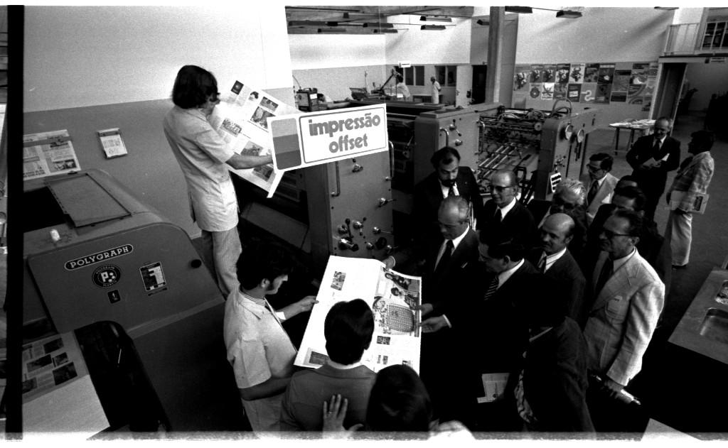 """Audiodescrição da imagem: Fotografia horizontal, preto e branco, em que um grupo de pessoas aparece junto a uma grande impressora, no interior de uma gráfica. No ângulo de cima para baixo e da esquerda para direita, uma impressora offset revestida de metal e, reunidos próximos a ela, dezoito homens e uma mulher, todos em pé, pele clara, com aproximadamente trinta e cinco a setenta anos, dispostos em diferentes posições. A impressora offset é retangular, dividida em quatro partes: uma de unidade de entrada, dois grupos impressores e a unidade de saída, com botões, chapas de metal, alavancas de acionamento e desligamento, apoios, esteira e cabos condutores. Um cartaz claro na horizontal, em letras escuras e de fôrma, está fixado no segundo grupo impressor, escrito: """"IMPRESSÃO OFFSET"""". No grupo de representantes, a maioria dos homens são calvos, vestem paletós que variam do claro e escuro, camisas claras e gravatas escuras, usam óculos de grau, carregam pastas ou maletas, com exceção de dois, que estão de jalecos. Dos homens de jaleco: um deles aparece em um nível mais alto do que os demais do grupo, e segura com as mãos um jornal aberto. Ele tem cabelo liso, escuro e até o pescoço, e cabeça abaixada. Mais abaixo e à direita dele, um outro homem virado para o lado direito, cabelo escuro, curto com costeletas e nariz adunco, também segura com as mãos um jornal aberto, mostrando-o para o restante do grupo que está próximo a ele. Mais afastados, à direita da imagem, dois dos homens conversam entre si. Em um outro compartimento da gráfica, outras duas pessoas de jaleco trabalham. Elas estão ao fundo da imagem, mais distantes. Próximo à impressora offset, do lado esquerdo da imagem, uma parede. Ela é subdividida entre o claro e escuro, que se estende da esquerda até a direita da imagem, por uma quebra, que vai dar no outro compartimento da gráfica. Do lado esquerdo da parede, um cartaz e um calendário fixados,  e do lado direito, no outro espaço, três pequenas janelas retan"""