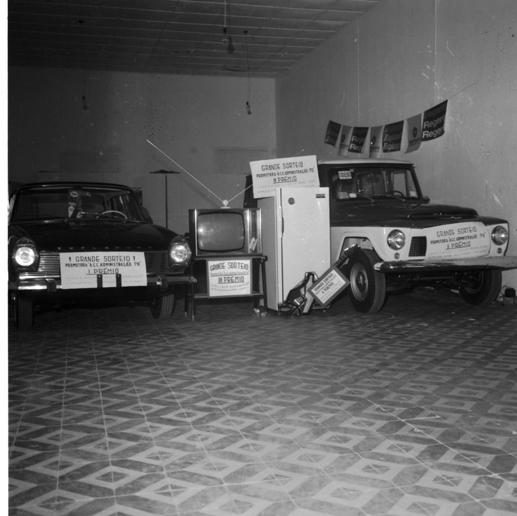 """Fotografia horizontal em preto e branco de cinco prêmios de um sorteio expostos em um local fechado. À extrema esquerda e de frente, um carro escuro, modelo semelhante ao Aero Willys de 1965, com faróis redondos, quatro portas, direção clara e as rodas de tamanho comum. Sobre o pára-choque dianteiro, uma placa horizontal e clara com a escrita: """"Grande Sorteio. Promotora """"ACC Administração70""""– I prêmio"""". Ao lado do carro, uma televisão escura, modelo análogo a Graetz dos anos 60 (das primeiras a cores), com caixa retangular de madeira, botões metálicos, redondos e posicionados na vertical, da metade para baixo em uma lateral junto à tela, onde acima está o alto-falante. Na parte superior da televisão, uma antena com base circular com duas hastes metálicas, finas e longas. O aparelho está sobre um balcão de madeira escura e com rodas, fechada apenas no fundo, tendo abaixo da tela, preso no balcão, uma placa horizontal e clara com a escrita: """"Grande Sorteio. Promotora """"ACC Administração70""""– III prêmio"""". Ao centro da imagem e a direita da televisão, uma geladeira clara,com uma linha vertical e metálica na extrema esquerda, onde encontra-se, a meia altura, o puxador do mesmo material. Acima, uma placa horizontal e clara com a escrita: """"Grande Sorteio. Promotora """"ACC Administração70""""– IV prêmio"""". Ao centro da imagem e à frente da geladeira, uma guitarra escura com detalhes claros no corpo do instrumento, semelhante a um modelo Warlock, com a base apoiada no chão e o braço escorado na roda dianteira de outro carro (o próximo prêmio). À frente da guitarra, uma placa clara, horizontal e menor que as demais, com a escrita: """"Grande Sorteio. Promotora """"ACC Administração70""""– V prêmio"""". A extrema direita e levemente voltado à direita, um carro da marca Ford Rural Willys, com a lataria em dois tons: o entorno das janelas e capô são escuros, enquanto o teto e restante do veículo é claro; tem faróis redondos, duas portas e rodas grandes. Sobre o pára-choque dianteiro, uma placa hori"""
