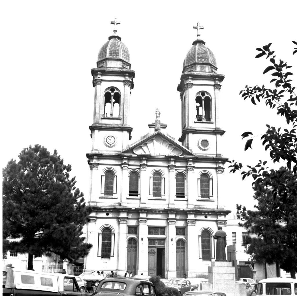 Audiodescrição da Imagem: Fotografia vertical em preto e branco da fachada de uma catedral em uma região urbanizada. A catedral é reta e alta, com dois andares e duas torres sineiras nas laterais. No primeiro andar há três portas e duas janelas. A porta principal, ao centro, é retangular, larga e de duas folhas, com a direita aberta, por onde se vê um breu. As portas nas laterais, uma de cada lado, também em duas folhas, têm a mesma altura que a principal, porém mais estreitas e com a parte superior arcada. Após, nas extremidades, dois vitrais de mesma largura que as portas laterais, de formato vertical e com a parte superior arcada. Já no segundo andar, os cinco vitrais têm a mesma largura, altura e arcada dos vitrais de baixo. Após o segundo andar estão as duas torres, uma de cada lado da fachada, com formato retangular na vertical, decoradas por arcadas, campanários, pilastras, capiteis e uma pequena cúpula ovalada no topo, com uma cruz acima. Na torre esquerda, pouco após o segundo andar, um relógio arredondado de ponteiros marca dez horas e um minuto; enquanto na direita, um vitral, de mesmo tamanho e formato do relógio. Entre as torres, um frontão de telhado em forma triangular, cuja fachada reflete o brilho do sol. Na extremidade superior do telhado, a estátua de uma mulher em pé, de frente e com vestes longas, a Imaculada Conceição, sobre um pedestal. Toda a arquitetura da catedral é monumental e suntuosa, com elementos predominantemente barrocos e neoclássicos. Seis pilastras frisadas fundem-se à fachada, de baixo até em cima, sendo que as duas em cada extremidade delineiam as torres até as cúpulas. Nos cinco vãos entre elas encontram-se as portas e janelas de cada andar. Capitéis, ábacos e arquitraves decoram cada uma das pilastras, na divisa do primeiro para o segundo andar e deste para as torres. Acima das portas há vitrais, quadrados sobre as portas laterais e retangular sobre a central. E todos os vitrais possuem finas linhas brancas horizontais e para