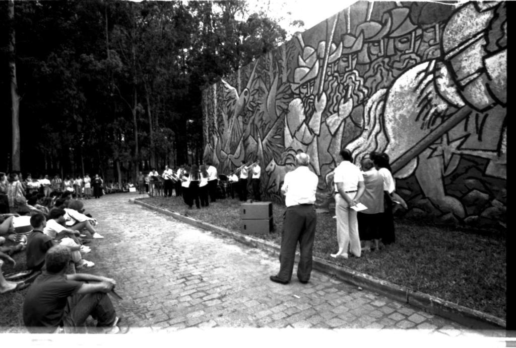 Audiodescrição da imagem: Fotografia horizontal em preto e branco de um mural artístico amplo, com inúmeras pessoas a sua frente, em um espaço aberto. O mural, de frente e levemente inclinado para a esquerda, é composto por uma arte pintada em um muro de concreto, com aproximadamente oito metros de altura por trinta metros de largura. A arte apresenta uma técnica de pintura com traços compridos, largos, escuros e em diferentes sentidos, formando elementos por vezes de fácil distinção, como homens de armadura, pássaros,  cavalo, pedras, e árvores, enquanto em outros pontos a identificação não é precisa. À frente do mural há um gramado em toda a sua extensão, com cerca de três metros de largura. Após esse gramado, uma rua de paralelepípedos que percorre toda a frente do mural e dobra-se à direita, formando uma esquina. Após a rua, outro gramado, bem maior que o primeiro e consequentemente, onde encontra-se a maior parte das pessoas presentes. As pessoas constituem um público diverso que assiste a um evento no local, espalhadas pelos dois gramados. São majoritariamente jovens, de perfil direito, sentadas sobre a grama, alguns estão em pé ao fundo do gramado maior, e vestem principalmente calças, blusas e casacos em tons claros e escuros. À frente esquerda do mural, sobre o gramado menor, um grupo de dez músicos, sendo oito homens e duas mulheres, em pé e de frente para o público. Eles vestem camisas claras e calças escuras, seguram instrumentos musicais  e têm à frente alguns suportes de partitura. Já na frente direita do mural, também sobre o gramado menor, em primeiro plano, quatro pessoas, sendo três homens e uma mulher, lado a lado e de costas para a imagem, com compleição física mediana e faixa etária entre quarenta e cinquenta anos. Deles, o primeiro e o último homens usam calças escuras e camisas claras, enquanto o outro usa calça e camisa clara e a mulher, saia escura e casaco claro; dois dos homens e a mulher têm cabelo escuro, o outro tem cabelo claro, sendo 