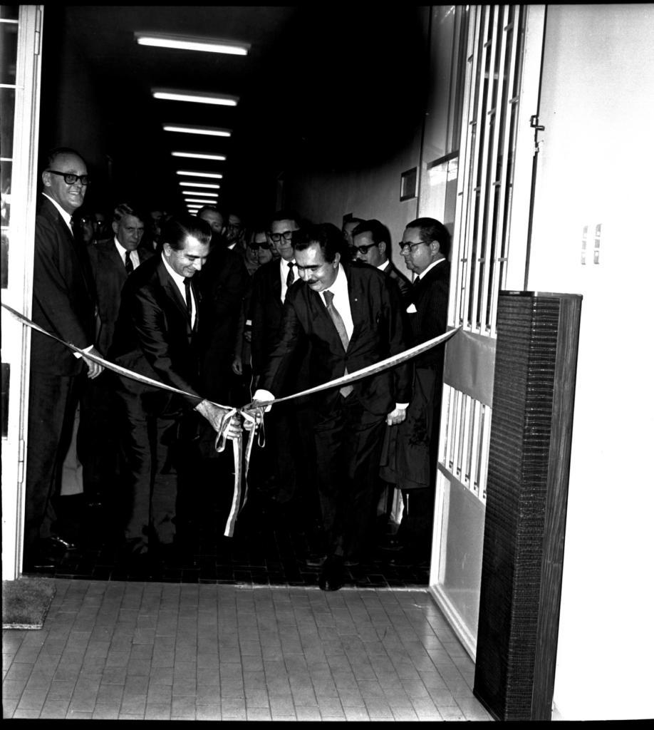 Fotografia vertical em preto e branco de dois homens junto a uma fita de inauguração, em um corredor, com outras pessoas ao redor, no interior de um ambiente fechado. Em primeiro plano, dois homens seguram as pontas de duas fitas, em laço, cujas extremidades opostas estão presas nas paredes do corredor. As fitas tem duas cores, uma clara e outra escura, na horizontal. Um dos homens, à esquerda e de perfil direito, olha e toca com a mão direita no laço, que está a sua frente. Ele tem a pele clara, cabelo liso, escuro e penteado para trás e usa um terno escuro com gravata escura e camisa clara.O outro homem, à direita e de frente para a imagem, toca com a mão direita na fita,ele tem a pele clara, cabelo escuro, liso e penteado para trás, bigode escuro e também veste um terno escuro com gravata escura e camisa clara. À frente e à esquerda, parte de uma porta de vidro e do piso, de madeira, liso. À direita, a outra parte daporta, com grades.As paredes são claras e lisas. Ao fundo, vários homens, vestindo terno e gravata escuros com camisas claras, olham diretamente para os dois homens que estão descerrando o laço da fita. Todos estão em pé, têm a pele clara e faixa etária de aproximadamente 50 anos. No teto, uma fileirade 10 lâmpadas fluorescentes.