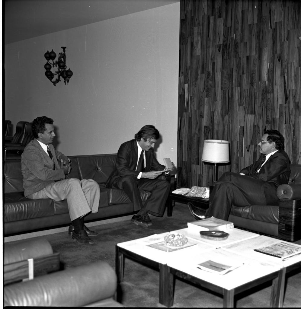 Audiodescrição da Imagem: Fotografia vertical em preto e branco, na diagonal da direita para a esquerda, de três homens sentados em dois sofás, que estão alinhados perpendicularmente. À esquerda da imagem, dois homens sentados em um sofá escuro com três lugares. O primeiro homem, de perfil direito, Tem aproximadamente quarenta anos, pele clara, cabelo curto, ondulado e escuro. Veste paletó com listras verticais, camisa e calça claras e gravata e sapato escuros. Está com o cotovelo esquerdo apoiado no encosto do sofá e os dedos das mãos entrelaçados. Olha a direita para o outro homem sentado no sofá. Ele tem aproximadamente trinta e cinco anos, pele clara, cabelo levemente comprido, liso e escuro. Veste terno e gravata escuros e liso, camisa clara e sapato escuro. Está com o corpo levemente voltado para a esquerda, inclinado para a frente, com os antebraços apoiados nos joelhos. Olha para uma pequena caixa clara que segura com as mãos e sorri. À direita da imagem, o terceiro homem. Está de perfil esquerdo, sentado em um sofá escuro de um lugar. Tem aproximadamente quarenta e cinco anos, pele clara, cabelo curto, ondulado e escuro. Veste terno e gravata escura, camisa clara e sapato escuro. Usa óculos de grau com armação clara. Está com as pernas cruzadas e olha para o homem que segura a caixa. Em  frente aos sofás, uma mesa baixa de madeira escura com tampo claro e quadrado, sobre ela quatro livros, uma folha de papel e dois objetos decorativos. A mesa está sobre um tapete grande e escuro. Atrás do encontro dos dois sofás, outra mesa, pequena e de madeira escura. Sobre ela dois papéis de embrulhos de presentes e uma luminária de mesa clara. Atrás do sofá de três lugares, visível o encosto de três cadeiras escuras encostadas em uma parede clara, que ocupa toda a largura da imagem e está atrás do sofá de um lugar. Uma luminária escura está presa na parede acima das cadeiras. Atrás do sofá de um lugar, a parede é revestida por um papel decorativo que imita madeira. O te