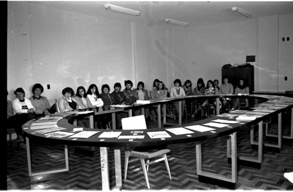Audiodescrição da imagem: Fotografia horizontal em preto e branco de um grupo de pessoas atrás de uma grande mesa oval em um ambiente fechado. O ângulo da imagem é diagonal da direita para a esquerda. O grupo é formado por dezesseis mulheres e dois homens, todos com pele clara, cabelos volumosos e escuros. Vestem roupas de frio, como casacos e blusões. Estão sentados e olham atentamente para a esquerda. O tampo da mesa é oval, comprido, vazado, escuro e sustentado por vários cavaletes claros. Sobre a mesa, folhas de papel. Ao centro da mesa uma cadeira clara. Ao fundo, o encontro de duas paredes claras. Na parede esquerda, um interruptor. Na parede direita, um armário de madeira escura, com duas portas, baixo e largo, e ainda, três interruptores. O teto é claro, com três lâmpadas fluorescentes. O chão é de parquets claros e escuros dispostos em zigue-zague. Audiodescritora Roteirista: Marya Eduarda Garcia de Oliveira Audiodescritora Consultora: Fernanda Taschetto