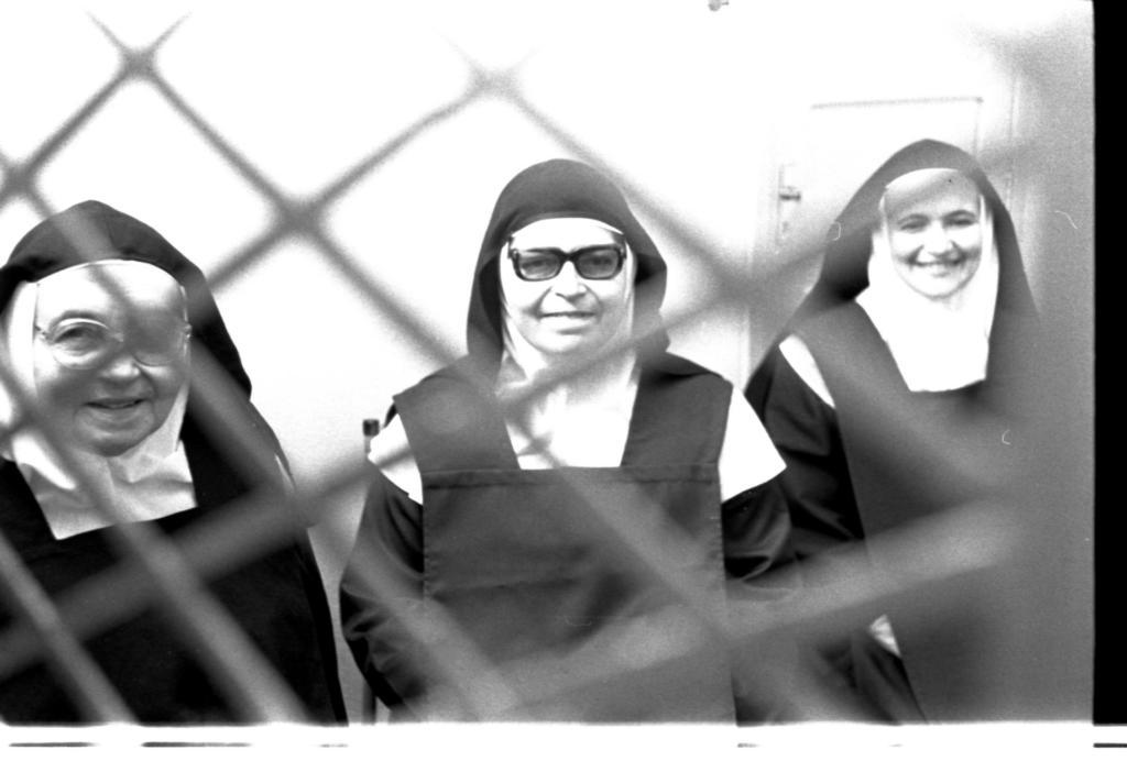 Audiodescrição da imagem: fotografia horizontal em preto e branco, na diagonal esquerda, de três monjas, uma ao lado da outra, em ambiente interno. Elas estão de frente e enquadradas da cintura para cima, vestem capuz escuro, limpel claro e hábito de corpo escuro. A monja da direita tem semblante neutro, cerca de 60 anos e usa óculos de grau com armação clara; a monja do centro tem semblante neutro, cerca de 50 anos e usa óculos de grau com armação escura; e a monja da esquerda tem cerca de 40 anos e sorri. A frente delas, próximo a imagem e desfocado, uma tela losangular de proteção clara. Ao fundo, parede clara e uma porta também clara.