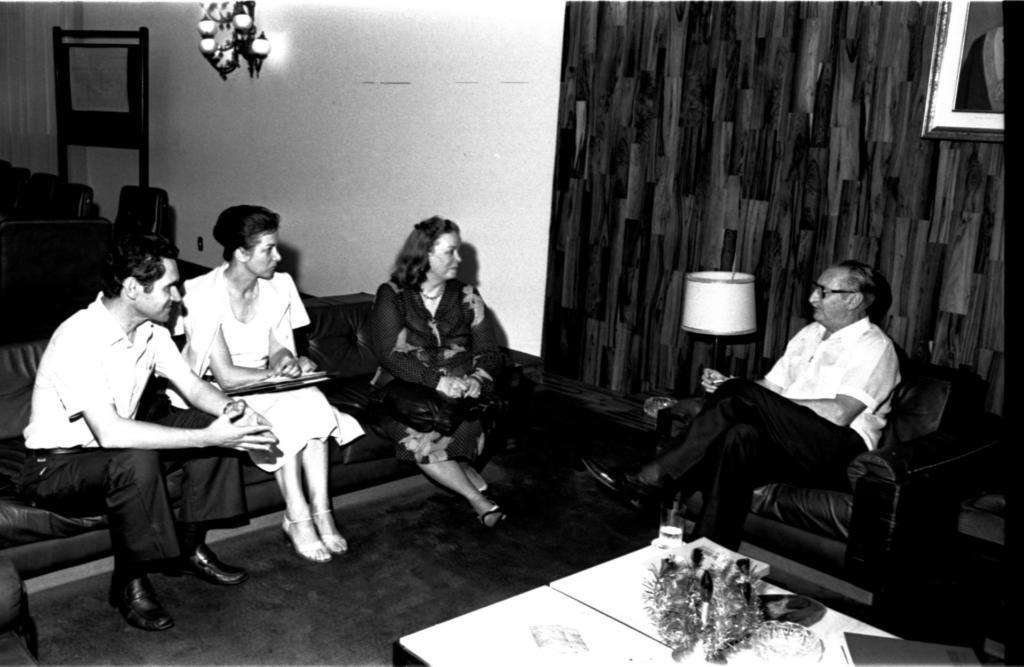 Audiodescrição da imagem: Fotografia horizontal em preto e branco, enquadrada em diagonal da esquerda para a direita,  de quatro pessoas sentadas em sofás. As pessoas, duas mulheres e dois homens, têm faixa etária de trinta a quarenta anos, pele clara e cabelos escuros. Estão sentados em sofás escuros, um de três lugares e o outro apenas de um lugar, posicionados perpendicularmente entre si. No sofá maior, à esquerda, está um dos homens e as duas mulheres. No outro sofá menor, o outro homem. As mulheres vestem vestidos na altura dos joelhos e sandálias de salto alto. Os homens, vestem camisa claras, calças e sapatos escuros. O homem à esquerda do sofá maior, está inclinado para frente, com os cotovelos apoiados nos joelhos e as mãos entrelaçadas. A mulher ao lado dele, está de vestido claro de mangas curtas e um blazer claro sobre os ombros. Os cabelos estão presos em um coque e segura uma pasta apoiada sobre as pernas. A outra mulher, está de vestido escuro, estampado com folhagens claras, de mangas compridas. O cabelo está solto, enfeitado com uma presilha. O homem sentado no sofá de um lugar, está com o corpo inclinado em direção às outras pessoas e tem as pernas cruzadas. À esquerda do sofá menor, um abajur claro sobre uma mesinha. Em frente aos sofás uma mesa clara, pequena e baixa, de tampo quadrado, com um ramo de folhagens  em um vaso e um livro sobre ela. Atrás do sofá maior, parte de uma mesa com tampo quadrado, com cadeiras escuras. Atrás do sofá menor, uma parede que ocupa o fundo da imagem. A parte esquerda desta parede é clara, com um lustre escuro fixado e próxima à ela, um mural de avisos. A parte direita da parede é amadeirada, escura e vê-se somente a ponta da moldura clara de um quadro. Ao fundo e à esquerda, o encontro desta parede com outra, coberta por uma cortina longa e clara. O chão é acarpetado e escuro. Audiodescritora Roteirista: Marya Eduarda Garcia de Oliveira Audiodescritora Consultora: Fernanda Taschetto e Rubia Steffens