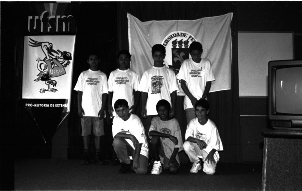 """Audiodescrição da imagem: Fotografia horizontal, em preto e branco, de sete meninos em um ambiente interno. No centro da imagem, quatro meninos em pé, e a frente deles, três meninos agachados. Eles estão de frente com o semblante neutro, o quarto menino em pé, está olhando para baixo. Eles tem faixa etária de dez anos, pele escura, cabelo curto e escuro. Seis deles vestem camisetas claras de manga curta, três com a escrita na camiseta """"Projeto Meninos no Campus"""", dois meninos vestem bermudas, dois vestem calça, outros três estão ocultos atrás dos meninos agachados, e a maioria usa tênis escuros. O menino agachado no meio veste camiseta e bermuda escuras. À esquerda da imagem, um cartaz vertical com o desenho de um quero-quero estilizado de gaúcho com chimarrão e pala, escrito acima """"UFSM"""", e abaixo do desenho """"Pró-Reitoria de Extensão"""". À direita da imagem, está visível parte de uma mesa escura, com uma televisão escura sobre ela. Ao fundo, cortina de tecido escura até o chão. Atrás dos meninos e presa na cortina, a bandeira da Universidade Federal de Santa Maria. À direita da bandeira, visível parte de uma parede e preso nela um quadro branco."""