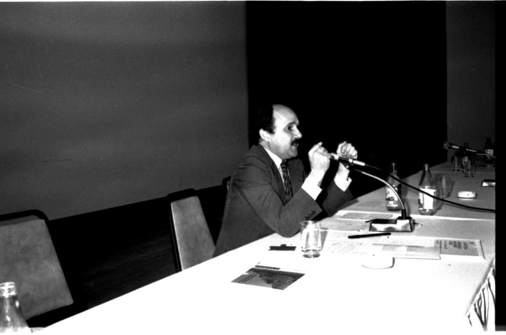 Audiodescrição da imagem: Fotografia, horizontal, em preto e branco. Um homem sentado em um ambiente claro. Há duas cadeiras visíveis na esquerda e o homem está sentado na segunda cadeira. Ele tem pele clara, cabelo curto, liso, escuro, com entrada calvinística e bigode escuro. Tem rosto oval e faixa etária de 50 anos. Está com os cotovelos sobre a mesa, com as mãos fechadas. Veste terno e gravata escuros e uma camisa clara. A sua frente um microfone de mesa. A mesa é retangular, com toalha clara. Em cima tem um copo transparente vazio, algumas folhas de escrever claras, uma caneta escura e duas garrafas transparentes vazias. Ao fundo uma parede lisa, clara. No lado direito uma parede escura em diagonal para foto.A foto foi tirada em diagonal da mesa, com flash.