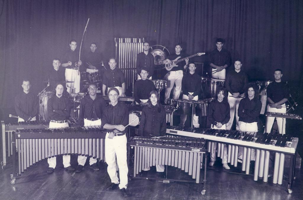 Audiodescrição da imagem: Fotografia em preto e branco, na horizontal, de um grupo de músicos em meio a vários instrumentos, enquadrados de corpo inteiro, em um ambiente interno. Posam para a fotografia, dezoito pessoas em pé e de frente, com seus instrumentos musicais, sobre um estrado. Elas tem cerca de 25 a 40 anos, aproximadamente 1,70 de altura, uma delas é mulher e um pouco mais baixa. O grupo é composto por dezesseis pessoas de pele clara e dois de pele escura, todos têm cabelo escuro; cinco dos homens têm cabelo comprido, dois estão com ele preso e outros dois são mais crespos, um deles usa barba e outro cavanhaque. Apenas três desses homens usam óculos. Toda a banda veste a mesma roupa, camisa escura, calça clara e sapato escuro social. Somente um dos homens usa tênis claro. Cada um dos músicos que compõe a banda traz consigo um instrumento musical ou está em pé atrás dele. Entre os instrumentos temos: bongos, marimbas, berimbau, baixo, teclados, tom-tom e conga. Em primeiro plano, no nível do chão, um homem com os braços cruzados segura uma batuta na mão direita e usa relógio no pulso esquerdo. Nos degraus acima, o restante da banda com seus instrumentos. Ao fundo da imagem, uma grande cortina escura na horizontal. O chão é escuro amadeirado. Audiodescritora Roteirista: Isabel Motta Audiodescritora Consultora: Rúbia Steffens