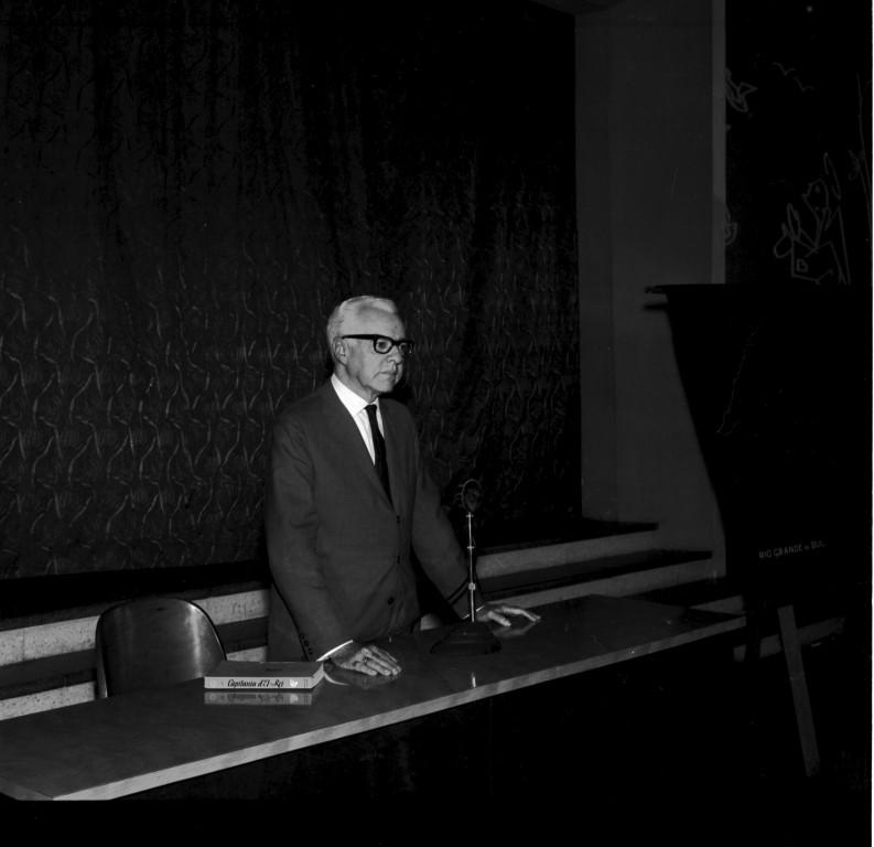 Fotografia vertical, em preto e branco, de homem em pé, enquadrado da cintura para cima, atrás de uma mesa. Ele tem pele clara e cabelos grisalhos, usa óculos de armação grossa escura e veste paletó escuro, camisa branca e gravata escura. Olha para frente e está com as mãos apoiadas na mesa. Sobre a mesa retangular de madeira,à esquerda um livro fechado e ao centro, um microfone em um pedestal metálico. À direita da mesa, um cavalete de madeira coberto parcialmente por um tecido escuro. Ao fundo, cortinas estampadas ocupam quase toda a largura da foto. Abaixo das cortinas quatro degraus de madeira. À direita, atrás do cavalete, uma parte de uma parede clara.
