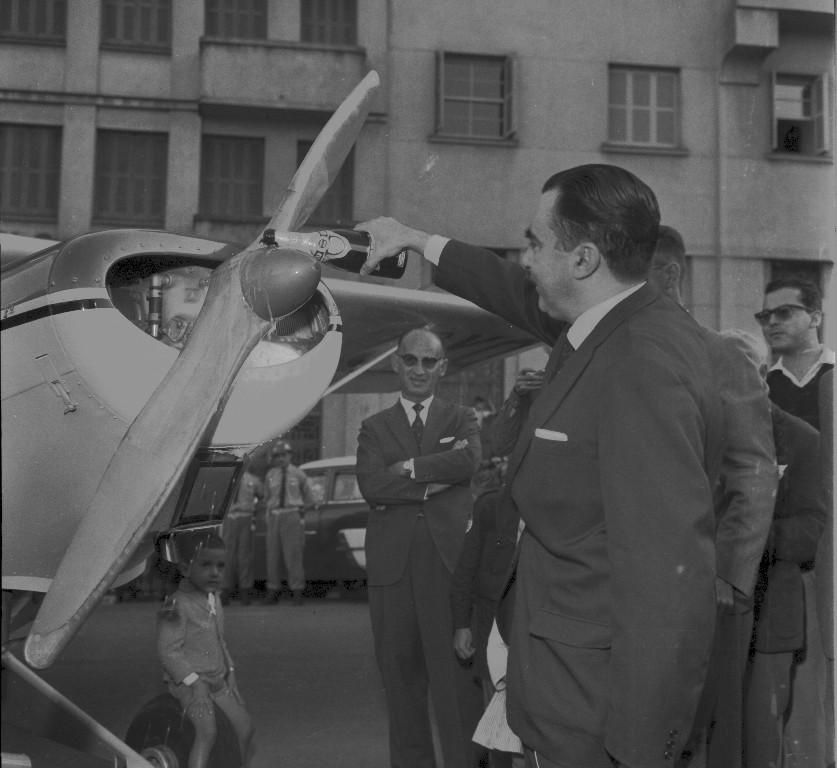 Fotografia quadrada em preto e branco de um senhor de pele clara e cabelos escuros e curtos, com terno e gravata, despejando espumante sobre a hélice de um avião. A parte frontal do avião, à esquerda, está virada para a direita, com a hélice de duas pás na extremidade. O senhor, à direita, segura a garrafa com a mão direita e sorri. Sentado sobre o trem de pouso dianteiro do avião, um menino de pele clara e cabelo curto e claro, com terno, gravata e bermuda.  Ao redor do homem, várias pessoas observam a ação. Ao fundo, um prédio que se vê até o terceiro andar e uma viatura com dois policiais ao lado.