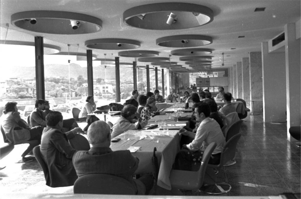 """Fotografia horizontal em preto e branco de aproximadamente 25 pessoas reunidas em uma sala.Elas estão sentadas em cadeiras, ao redor de mesas, estando duas de costas e as demais de perfil. A maioria das pessoas são homens, de pele clara e cabelos escuros.Alguns usam ternos escuros e outros, camisas claras de mangas longas. As mesas estão lado a lado, no centro da sala. O conjunto das mesas forma um """"T"""" e sobre elas há copos, papéis e toalhas de mesa.À esquerda e à frente da foto, outras três pessoas sentadas em cadeiras. E, atrás delas, mais uma pessoa sentada, com os cotovelos apoiados sobre uma mesa. A sala é comprida, com o teto e as paredes da esquerda, do fundo e da direita.No teto, de cor clara, há duas fileiras de luminárias com aproximadamente 16 espaços redondos e côncavos, com dois spots articulados de lâmpadas no interior. Essas fileiras estão no centro da sala, da frente até o fundo. Na parede da esquerda há amplas janelas de vidro, divididas por sete pilares pretos e finos. Ao fundo, a parede é de vidro, com um mural à direita e uma pessoa. E, à direita, sete pilares largos de tons claros. Pelas janelas de vidro à esquerda e ao fundo avista-se o ambiente externo, com carros estacionados, um prédio de dois andares, algumas casas e árvores."""