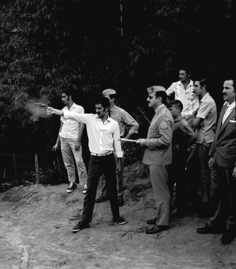 Fotografia vertical em preto e branco de um grupo de oito homens, em pé, reunidos em um terreno ao ar livre. No centro da imagem, um homem, de frente, enquadrado por inteiro, atira com um revolver, que segura com o braço direito estendido à esquerda. O atirador tem estatura e tom de pele médios, cabelo e bigode escuros, usa calça e tênis escuros e uma camisa clara; está com o rosto de perfil e o olhar fixo para a esquerda, na direção em que atirou, com os olhos serrados, quase fechados. O revólver é pequeno, calibre 38, de tom médio e está rodeado de fumaça. Os outros sete homens observam a cena, a maioria enquadrados por inteiro e de perfil esquerdo. Dois deles estão posicionados às costas do atirador. O primeiro tem pele clara e cabelos escuros, usa camisa clara de manga curta, calça jeans e tênis. O outro tem pele clara, cabelo escuro e usa uniforme militar, com chapéu, camisa clara de mangas longas, calça e sapato social, e está com a mão esquerda na cintura. Ao lado do braço esquerdo do atirador, outro homem, também com uniforme militar, tem a pele clara, cabelo e bigode escuros; Usa óculos escuro, chapéu, casaco militar com detalhes no ombro e na manga, bolsos largos no peito e na parte inferior da peça, mais calça social e sapato social, escuros. Ele segura uma prancheta e, as suas costas, o quarto homem, que destaca-se pela estatura mais baixa do grupo, aparentando ser mais novo. Este tem pele de tom escuro, cabelo escuro e curto, usa camisa e calça escuros e também tem a mão esquerda na cintura. Atrás dele, outros três homens: o primeiro, ao fundo, enquadrado da cintura para cima, tem a pele de tom médio e cabelo e bigode escuros, usando camisa clara com mangas curtas; o segundo tem pele clara e cabelos escuros, usa camiseta clara de mangas curtas e está de braços cruzados; e o último homem, posicionado na borda direita da foto, tem pele clara, cabelo e bigode escuros, usa terno e gravata escuros, camisa branca e está com o terno abotoado. Ao fundo, árvores