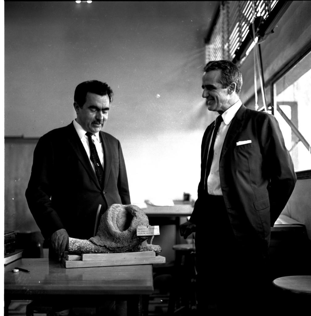 Audiodescrição da imagem: Fotografia horizontal, em preto e branco. Dois homens em um ambiente interno. Ao lado esquerdo da foto, um homem em pé, enquadrado da cintura para cima, de terno escuro, gravata escura e camisa clara. Pele clara, cabelo liso, escuro, sobrancelha larga e escura, bigode escuro. Está com o olhar voltado para baixo. A frente dele uma mesa escura de madeira, sobre ela uma base de madeira, que contém um galho de árvore com uma casa redonda de João-de-Barro. Na qual o homem apoia os dedos da mão direita. Ao lado direito, outro homem enquadrado dos joelhos para cima, com pele clara, cabelo escuro, com expressão facial sorridente. Usa terno e gravata escuros, camisa clara e calça escura. Tem um lenço claro no bolço do terno. Ao fundo uma mesa clara com alguns objetos em cima. Após, uma parede alta, lisa, clara. No lado direito há duas janelas, grandes, na horizontal, uma na parte inferior e outra na parte superior da parede.
