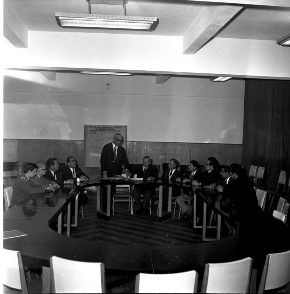 Audiodescrição da imagem:Fotografia horizontal, em preto e branco, de 11 homens em volta de uma mesa oval, em um ambiente interno. Os homens têm faixas etárias entre 20 e 55 anos, pele clara, vestem terno e estão sentados juntos a uma mesa, olhando para o único homem que está em pé. O primeiro homem, tem cabelo liso, curto e escuro, veste terno acinzentado e tem os braços sobre a mesa. A direita dele, o segundo homem, tem cabelo liso, curto e claro, veste terno acinzentado e óculos escuro, tem os braços sobre a mesa. O terceiro homem tem cabelo liso, levemente volumoso e escuro; o quarto homem cabelo liso, curto e escuro, eles vestem terno e gravata escura, e camisa clara. Eles também estão com os braços sobre a mesa. O quinto homem está em pé, cabelo liso, curto e claro, usa terno e óculos escuros. Está com a mão esquerda sobre papeis em cima da mesa. O sexto homem tem cabelo liso, curto, com entradas de calvície e claro, e tem o braço esquerdo sobre a mesa. O sétimo homem tem cabelo liso, curto e escuro com algumas partes claras. O oitavo homem tem cabelo levemente volumoso, curto e escuro e tem os braços sobre a mesa. O nono homem tem cabelo levemente ondulado e curto, e escuro. Usa óculos escuro e tem os braços sobre a mesa com os dedos entrelaçados. O décimo e o décimo primeiro homem, tem cabelo curto, liso e escuro, e tem os braços sobre a mesa. A mesa é grande, de madeira escura, tem formato oval com o centro vazado, e suporta lugar para cerca de 20 pessoas. As cadeiras são de madeira escura e estofado claro. Ao fundo, atrás do quinto homem, preso na parede, um mapa de fundo claro do Estado do Rio Grande do Sul, acima um crucifixo pequeno de madeira. A parede tem a metade inferior escura e a metade superior clara. A direita, parede coberta por cortina escura. Teto claro com estruturas horizontais e verticais de sustentação, com lâmpadas florescentes. O chão é escuro com linhas acinzentadas em curva.