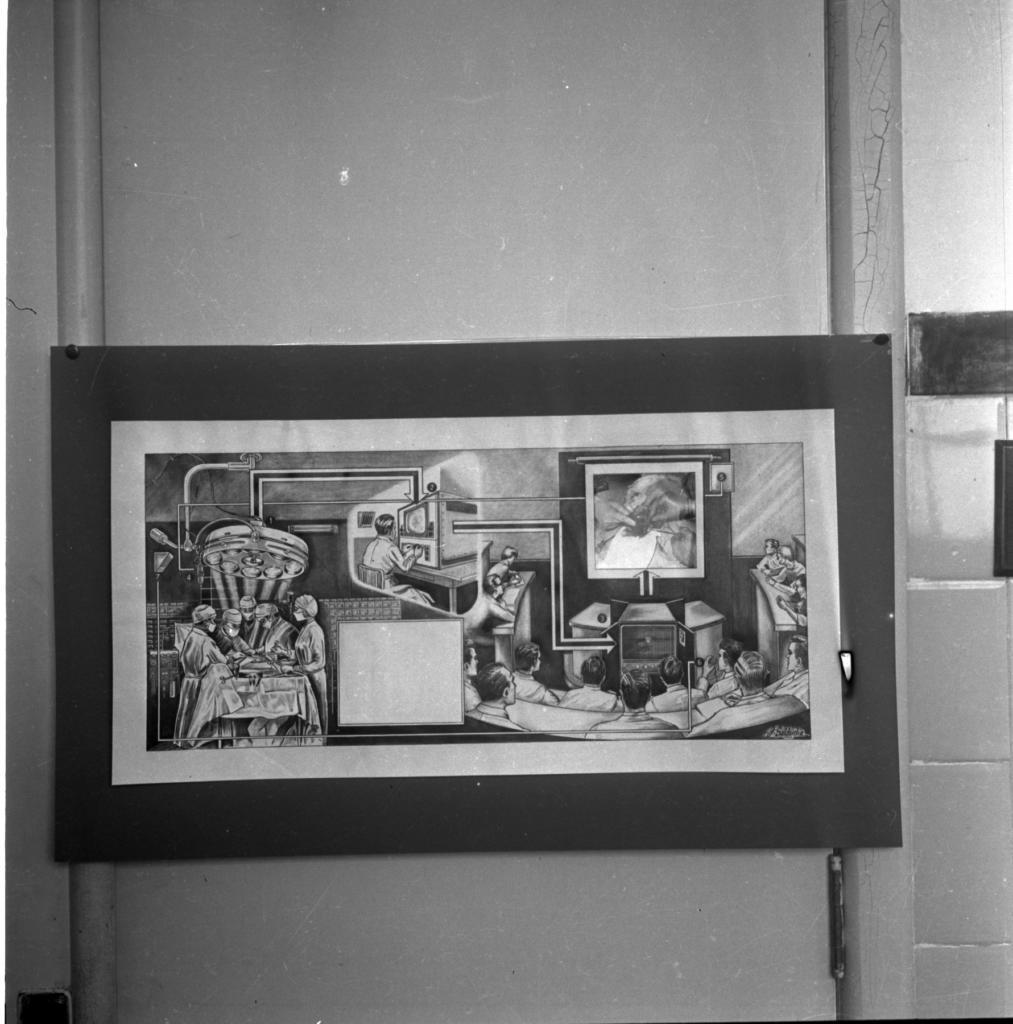 Audiodescrição da imagem:Fotografia, horizontal, em preto e branco. Um quadro com desenho ilustrando uma sala de cirurgia. O quadro tem as bordas escuras, grossas, e uma listra clara mais fina em volta de todo o quadro. Os desenhos são feitos em tons claros e escuros. Na esquerda tem cinco pessoas vestindo trajes cirúrgicos: toucas, máscaras e roupão. Elas estão em volta de uma mesa cirúrgica; acima da mesa tem uma luminária redonda. Destacado por uma claridade maior ao centro da imagem, um homem sentado, está de frente para uma televisão. A direita da imagem, doze homens sentados em formação de um U de costas para a fotografia, assistindo a cirurgia na imagem projetada em um telão. O quadro está localizado em um ambiente interno , com paredes brancas.