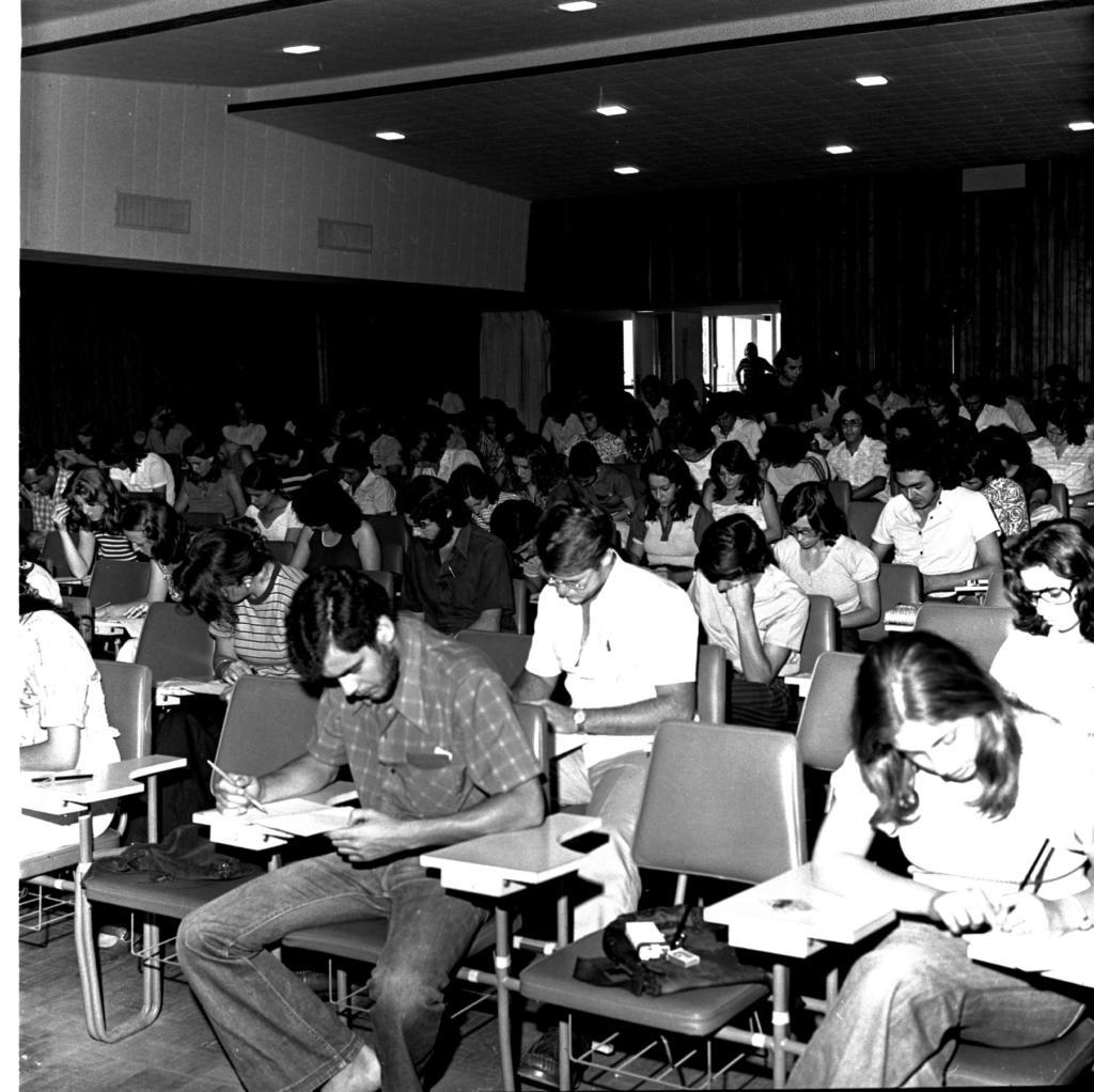 Audiodescrição da imagem: Fotografia vertical em preto e branco, enquadrada levemente da direita para a esquerda,  de um grupo de pessoas sentadas em cadeiras escolares. O canto inferior direito da imagem está mais claro. São aproximadamente 60 jovens na faixa etária entre dezoito e trinta anos, a maioria mulheres. Eles estão sentados, enquadrados dos joelhos para cima, com as cabeças abaixadas e expressões concentradas, lendo ou escrevendo em folhas de papel que estão em frente a eles.  Vestem roupas casuais, como blusas, camisas e calças. Na primeira fileira, à esquerda, parte do corpo de uma mulher. Ao lado, um jovem sentado entre duas cadeiras com bolsas escuras em cima. Ele tem cabelo e barba escuros, veste camisa xadrez e segura com a mão direita um lápis e com a mão esquerda uma folha de papel. À direita na mesma fileira, uma jovem está sentada de pernas cruzadas e escreve em uma folha de papel. Na segunda fileira, atrás do homem da primeira,outro homem, com cabelos claros, veste camisa e calça claras, usa óculos e relógio no pulso esquerdo. As cadeiras estão organizadas uma ao lado da outra, em fileiras. São escuras, estofadas e com braço de apoio para material. Ao fundo, o encontro de duas paredes. À esquerda, uma parede larga dividida em duas partes, a de cima clara com duas caixas de som fixadas e a de baixo escura. à direita uma parede amadeirada, com uma porta larga aberta, por onde entra luminosidade e pode-se ver outro ambiente com janelas retangulares de vidro.  Em frente à porta, a silhueta de um homem com as mãos na cintura. O teto é claro, com sancas e oito pequenas lâmpadas retangulares acesas.   Audiodescritora Roteirista: Isabel Motta. Audiodescritora Consultora: Fernanda Taschetto