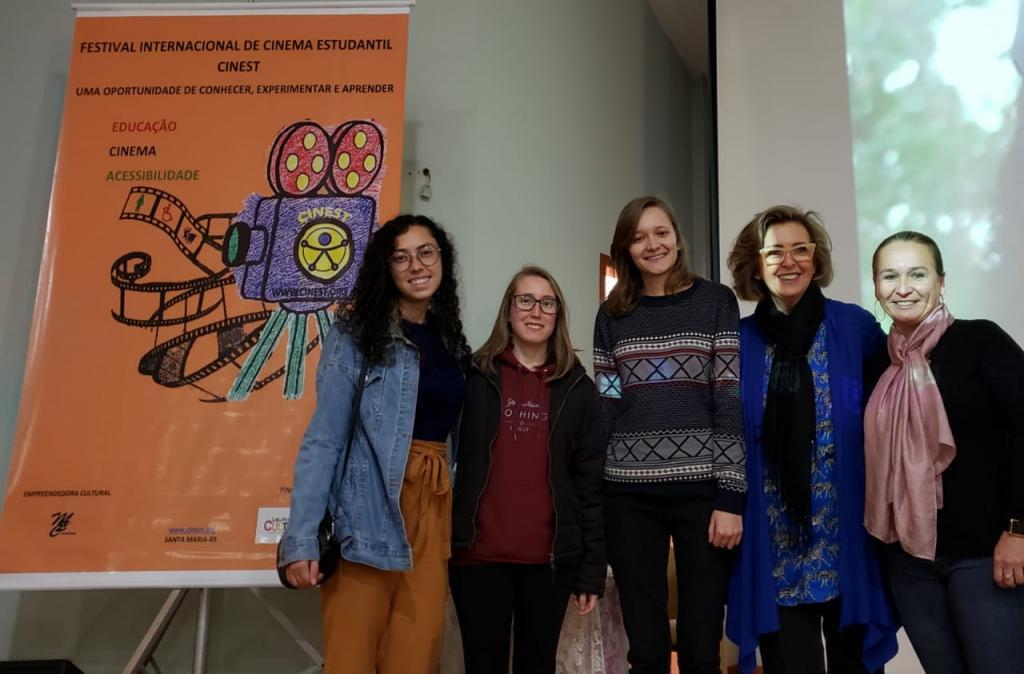 Fotografia horizontal colorida de cinco mulheres sorrindo ao lado do banner do Festival de Cinema Estudantil