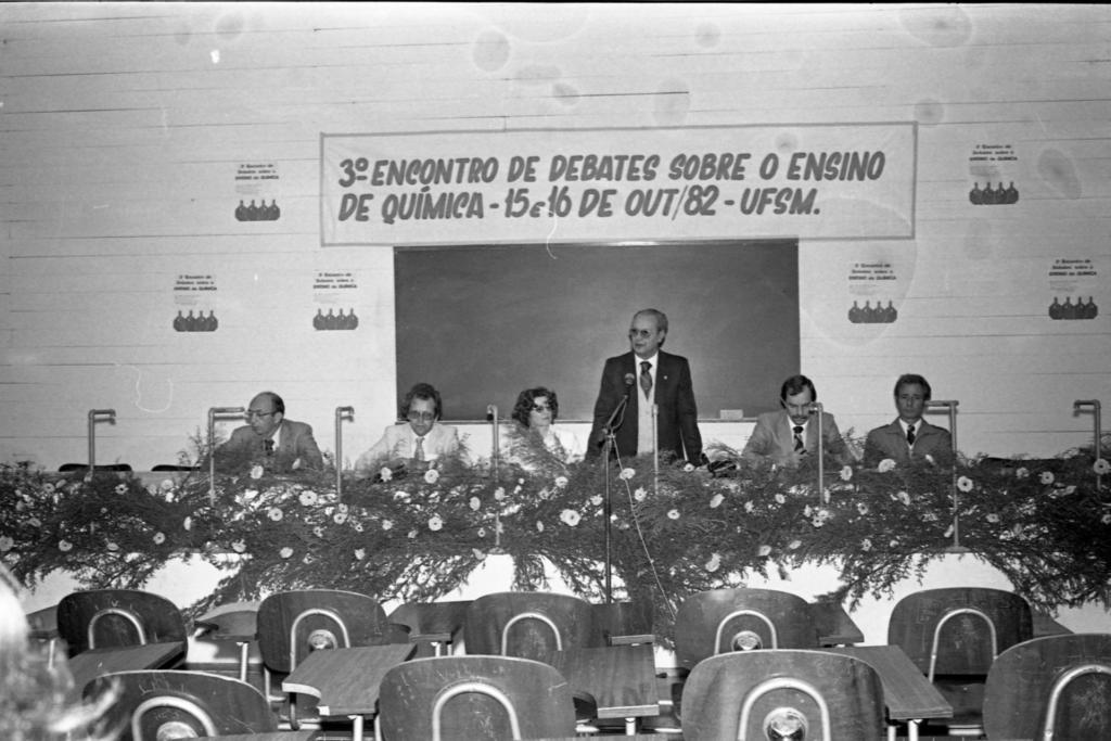 """Fotografia horizontal, em preto e branco, ambiente fechado, ao centro um homem em pé, em frente a um microfone, ao seu redor quatro homens e uma mulher sentados, todos posicionados atrás de uma mesa. Ao centro da imagem, um senhor em pé, posicionado atrás de uma mesa retangular e cumprida, com um microfone fixado sobre a mesa a sua frente, enquadrado da cintura para cima, perfil direito levemente voltado para a esquerda,mãos apoiadas sobre a mesa, é calvo, cabelo ralo e liso, pele clara, usa óculos, veste terno escuro, por baixo camisa branca de gola fechada, e sobre ela um cardigan de botões e gola """"V"""" profunda, em tom claro, gravata escura. A esquerda do homem, uma mulher e dois homens sentados, na ponta esquerda da mesa um senhor enquadrado do peito para cima, é calvo, cabelo escuro, usa óculos, nariz fino e cumprido, boca pequena, orelhas grandes, veste terno escuro, por baixo camisa branca de gola fechada, gravata escura, os antebraços estão sobre a mesa. A sua direita um homem enquadrado do peito para cima, tem cabelo cheio, escuro, com entradas na testa, usa óculos, veste terno claro, por baixo camisa branca de gola fechada, gravata clara, os antebraços estão sobre a mesa e as mãos estão cruzadas, olha para frente. A sua direita uma mulher sentada, tem cabelo volumoso escuro, usa óculos, veste roupa clara, está com a cabeça voltada para a direita. A sua direita o homem ao microfone, a direita dele um homem sentado, cabelo liso, escuro, com entradas na testa, bigode escuro, veste terno também escuro, por baixo camisa branca de gola fechada, gravata escura, olha para baixo em direção a mesa, tem os antebraços sobre a mesa. A sua direita um homem sentado em posição ereta, olha para frente, tem cabelo volumoso, escuro, olhos e boca pequenos, veste jaqueta escura, camisa de gola branca fechada, gravata escura. Na parte inferior da imagem, nove cadeiras universitárias, enfileiradas uma ao lado da outra, em duas filas, as cadeiras tem prancheta fixa, de madeira em f"""