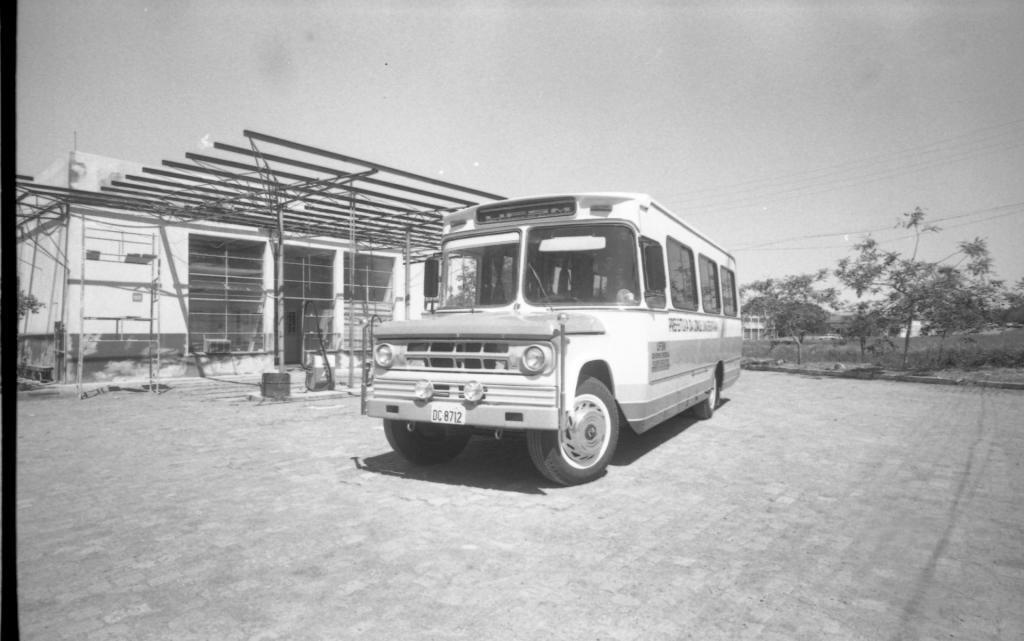 Fotografia retangular, em preto e branco, ao centro, em destaque um micro ônibus estacionado lateralmente. O local é o setor de transportes da UFSM. O micro ônibus está estacionado lateralmente em um pátio largo, de paralelepípedos, em frente a uma construção. O veículo de cor clara, é antigo, com aproximadamente 4 metros de comprimento. A parte da frente é larga e o capô, mais escuro que a pintura do restante do veículo, é semelhante ao de uma camionete, se alongando a partir de dois para-brisas dianteiros. No alto há uma placa de identificação escrito UFSM em letras claras sobre um fundo escuro. No para-brisa da direita o quebra-sol está abaixado e o limpador levantado. Na parte frontal do micro ônibus, há uma grade com 8 retângulos vazados ladeada por dois faróis. Abaixo da grade há dois faroletes centralizados e sob eles o para-choque com uma placa clara com a escrita em letras maiúsculas e escuras DC8712, centralizada. Os quatro pneus são de borracha escura com calotas de metal prata, sendo que os dois da frente estão ligeiramente voltados para a esquerda. Em cada lateral do capô, a frente, há preso um enfeite em forma de bastão com uma bola prateada em cima. Na lateral do micro ônibus há quatro janelas, a primeira, menor na cabine do motorista e as outras três na cabine dos passageiros. Abaixo das janelas maiores a frase Prefeitura da Cidade Universitária está pintada em letras escuras e maiúsculas. Sob a frase, uma faixa larga de cor mais escura percorre toda a lateral da carroceria. No início desta faixa, abaixo da janela do motorista pintado em letras maiúsculas e distribuídas em 3 linhas a frase UFSM, GOVERNO FEDERAL, PODER EXECUTIVO. Uma faixa clara seguida de duas faixas mais escuras finaliza a pintura da lateral do veículo. No lado esquerdo da fotografia, paralelo ao veículo, um prédio de alvenaria, térreo, retangular, com 3 janelas com básculas em toda altura da parede. As janelas são de metal, as básculas de vidro, cada janela tem 12 básculas, sendo q