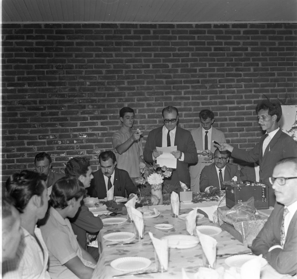 Audiodescrição da imagem: Fotografia quadrada, em preto e branco, de um grupo de treze pessoas em uma sala com paredes de tijolo a vista e teto alto, de tábuas de madeira, pintada de cor clara com uma moldura de madeira também de cor clara. As pessoas, espalhadas na sala, estão em divididas em dois grupos, um em pé e um sentado ao redor de uma mesa em forma de L invertido. O grupo que está em pé, centralizado na fotografia, encontra-se ao fundo, atrás da mesa, próximo a parede de tijolos, de frente para o fotógrafo. Da esquerda para a direita um jovem, branco, de cabelo curto e escuro. Veste camisa clara, de mangas curtas, abotoada até o pescoço. Tem o braço direito levantado e dobrado em frente ao corpo, segurando um dispositivo de gravação de cor clara, com um fio comprido. Ao seu lado, o prefeito da cidade de ITAQUI faz a leitura do projeto elaborado pela Assessoria de Planejamento da UFSM que visava o desenvolvimento socioeconômico do município. É um homem, branco, vestindo terno escuro, camisa branca e gravata preta. Tem os braços dobrados em frente ao corpo e nas mãos segura uma folha de papel. Seu cabelo é escuro e ele é ligeiramente calvo. Usa óculos com aros escuros. Ao lado dele, um homem magro, branco, de cabelo e bigode escuros, veste um terno claro, com camisa branca e gravata escura. Ele tem nas mãos um aparelho gravador em formato de caixa e está olhando para o aparelho. Em frente a mesa, o quarto homem em pé está de perfil. Ele é branco, tem cabelo farto e escuro. Usa bigode bem aparado. Veste um terno escuro, com camisa branca e gravata. Seu braço está estendido em direção ao homem que está lendo o papel e segura um pequeno microfone com um longo fio escuro. A sua frente, sobre uma mesa de apoio, separada da mesa principal em forma de L invertido, um gravador antigo, de formato retangular e com duas fitas de rolo. As demais pessoas da fotografia estão sentadas ao redor da mesa. Na parte próxima à parede do fundo da sala, a toalha que cobre a mesa é 