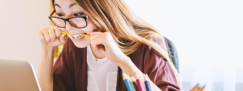 Mulher asiática usando óculos morde lápis ao olhar para tela do computador.