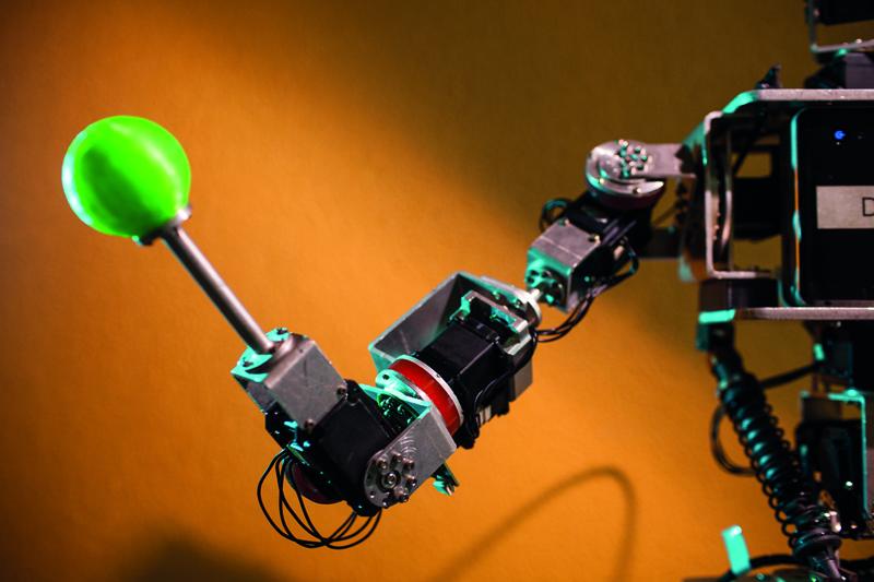 Detalhe do braço do robô Dimitri, que mostra a parte da série elástica em vermelho. Na mão do robô há um objeto verde de ponta arredondada.