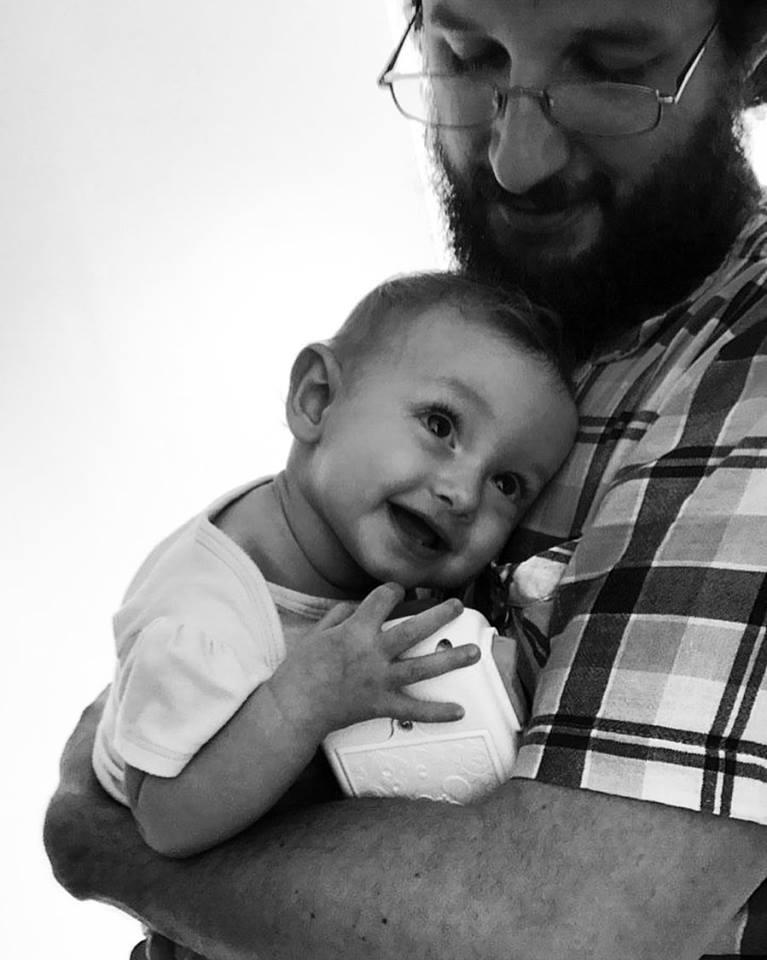 Homem de barba e óculos com um bebê no colo