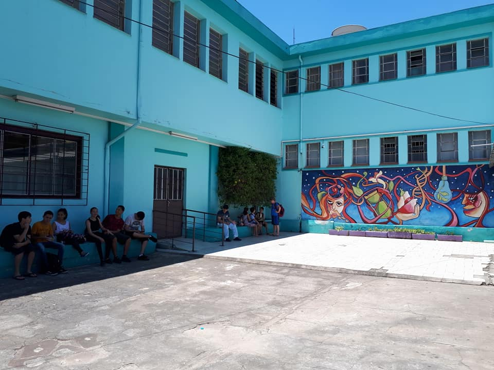Descrição da imagem: foto mostra em ângulo de 45º o interior do colégio, com duas faces internas, incluindo uma vista parcial do mural no canto à direita e os dez estudantes no canto à esquerda. As paredes do colégio estão na cor verde clara e há várias janelas e básculas. No canto inferior, está o cão.