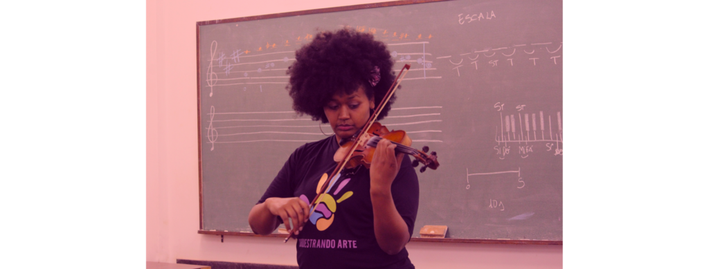 Em primeiro plano, moça toca violino. Ao fundo, quadro com partituras escritas com giz