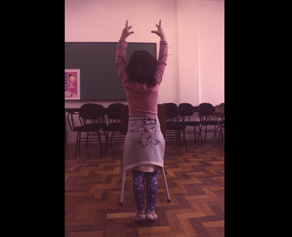 Menina em pé faz gesto com as mãos para cima e empina os pés
