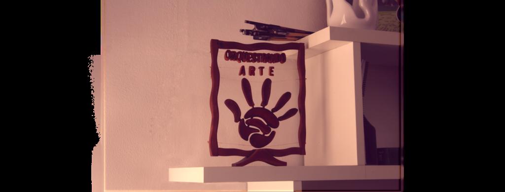 """Quadro em madeira mostra mão e o nome do projeto """"Orquestrando Arte"""""""