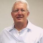 Foto vertical de homem usando óculos de grau e vestindo jaleco branco