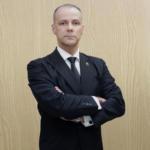 Foto horizontal de homem com braços cruzados usando camisa branca, terno e gravata pretos
