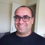Foto vertical de rosto de homem usanso óculos de grau e moletom preto