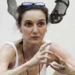 Foto quadrada de mulher falando e gesticulando, cabelos presos, óculos na cabeça e blusa branca
