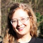 Foto quadrado de rosto de mulher loira sorrindo usando óculos de grau