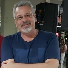 Foto quadrada de homem de baços cruzados vestindo camiseta azul escuro