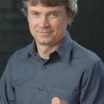 Foto vertical de homem com camisa cinza chumbo escrito UFSM, fundo preto