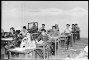 Descrição de Imagem: Fotografia horizontal em preto e branco de uma sala de aula com 11 pessoas sentadas em cadeiras de madeira atrás de mesas de madeira. As pessoas estão distribuídas em três fileiras. Sobre todas as mesas, um papel retangular claro. Em primeiro plano, na fileira do meio, mulher com pele em tom claro, na faixa etária dos 20 anos e com blusa estampada; ela apoia a mão no rosto e olha para frente. Atrás, um homem de pele clara e de cabelos escuros; ele coloca as mãos sobre a mesa, possui um relógio no pulso. Atrás dele, um homem de pele clara e cabelos escuros. Posterior, um lugar vago e, no fundo da sala, um homem e duas mulheres dispostos da mesma maneira. Na fileira do lado esquerdo, mulher de pele clara, na faixa dos 20 anos, de cabelos curtos e de vestido estampado em flores. Ela olha para o papel sobre a mesa. Atrás, estão mais três pessoas, sendo dois homens e uma mulher. No fundo da imagem, há outro homem de pele clara sentado, com um quadrado desenhado na parede atrás dele. A parede da sala é clara e o chão de azulejo quadriculado.
