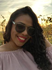 Descrição de imagem: Fotografia vertical e colorida de uma mulher jovem, com faixa etária de 25 anos, que sorri. Ela está enquadrada no centro da foto, em primeiro plano. Ela tem pele negra, olhos escuros, cabelos castanho escuros, ondulados e de comprimento médio. Usa óculos escuros. Sua cabeça está levemente inclinada para a direita da imagem e direciona o braço esquerdo até a cabeça. Ela veste uma camiseta na cor rosa bebê, uma correntinha no pescoço e uma pulseira na mão direita; a corrente e a pulseira têm tom dourado. Atrás, parreiras de uva e iluminação do sol presente.