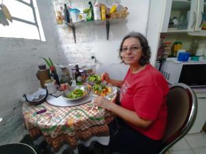 Descrição de Imagem: Fotografia horizontal e colorida de Roselaine sentada à uma mesa. Ela tem a pele branca, olhos escuros e cabelos na altura do ombro e grisalhos. Usa óculos e veste uma camiseta na cor vermelha e calça na cor azul escuro. Ela sorri levemente para a câmera. Está sentada em uma cadeira bege na cozinha; apoia as mãos na mesa e segura um garfo e uma faca por cima de um prato com legumes nas cores verde, amarelo e vermelho. A mesa é coberta por uma toalha estampada em xadrez, com cores predominantes em tons vermelho e verde. Sobre a toalha, há pratos com verduras coloridas e outros objetos. No fundo há uma parede branca. No lado esquerdo, uma janela; ao centro, uma prateleira de vidro com utensílios de cozinha e alimentos; canto direito, uma estante e um microondas, ambos na cor branca. O chão é de cerâmica branca.