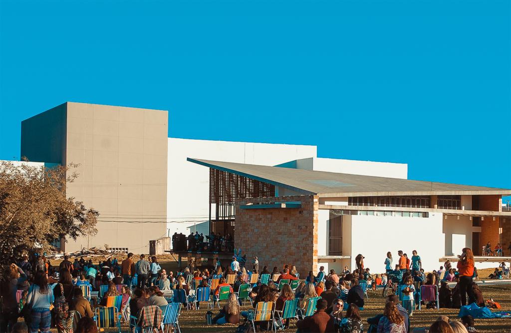 Foto de uma das edições do projeto Viva o Campus no espaço multiuso: Um dia ensolarado e de céu azul sem nuvem alguma. Há um prédio maior ao fundo e um outro prédio no formato de uma casa, logo a frente com uma varanda elevada, que funciona como palco, onde uma banda toca para um público de dezenas de pessoas que estão sentadas em cadeiras de descanso ou sentadas diretamente na grama. Parte de uma árvore aparece no canto esquerdo da foto.