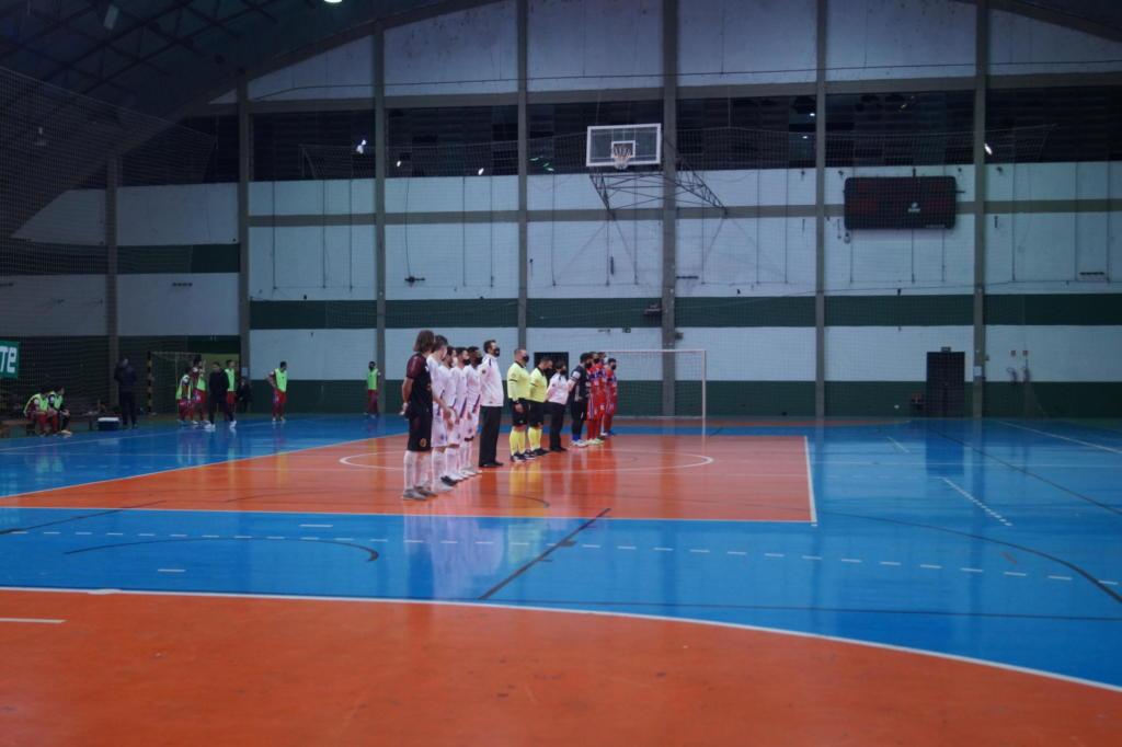 Foto horizontal e colorida de um ginásio de esportes, onde dois times de futsal estão organizados lado a lado, esperando o início da partida.