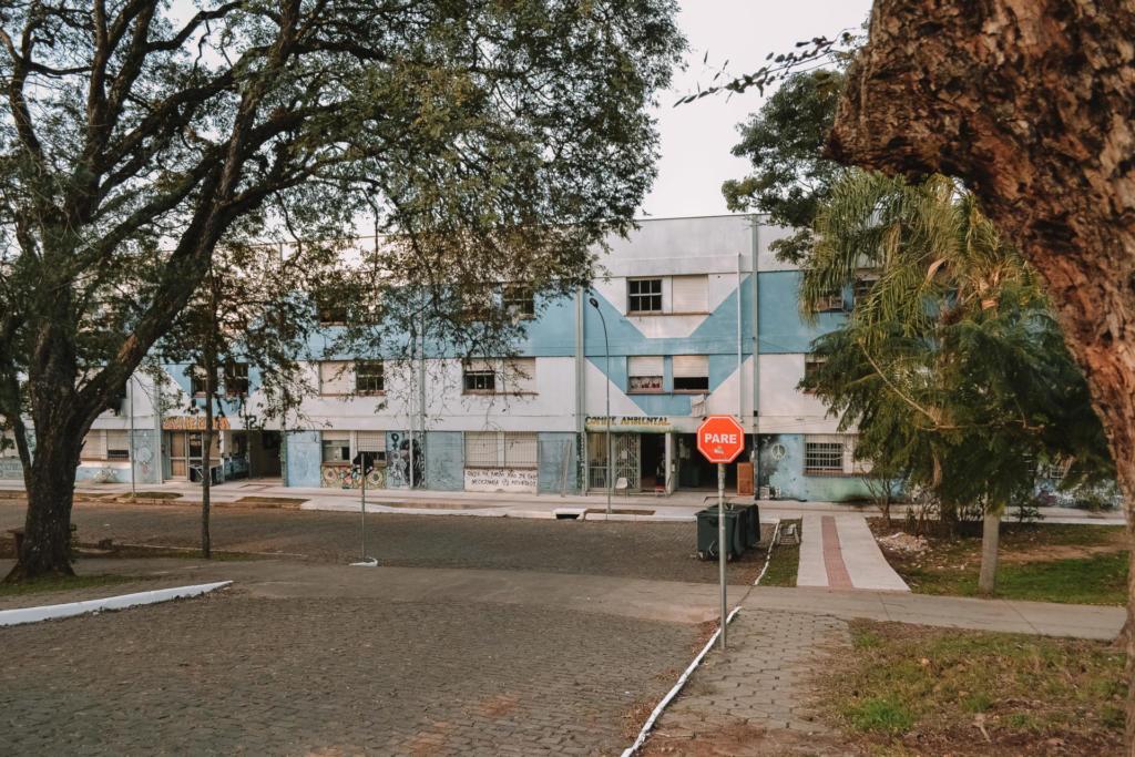 Fotografia horizontal de um prédio de três pavimentos na cor branca. Ele tem detalhes na cor azul no terceiro e primeiro pavimento. Na frente, uma rua, pavimentada em paralelepípedos, encontra o prédio e segue para a esquerda. Algumas das janelas estão abertas, outras fechadas. Há árvores em ambos os lados da rua e uma placa de 'PARE' na calçada à direita.