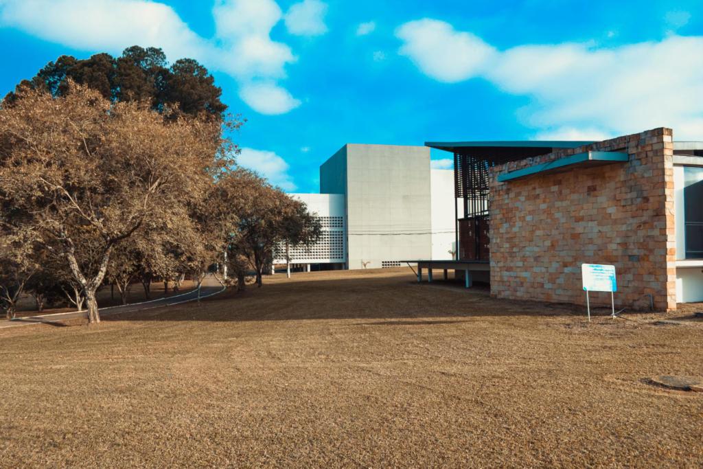 Foto do espaço multiuso durante a pandemia: Um dia ensolarado e de céu azul com poucas nuvens. Há um prédio maior ao fundo e um outro no formato de uma casa logo a frente com uma varanda. Na área aberta, em frente a varanda elevada existe uma área aberta com grama e na esquerda da foto há um pequeno caminho cercado por árvores.