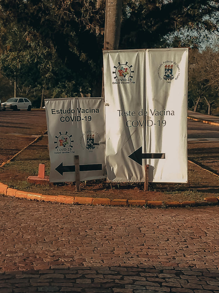 A foto mostra duas placas brancas cravadas na terra, uma pequena à esquerda e outra maior, à direita. As placas estão uma ao lado da outra, no canteiro central de uma avenida com pavimentação em paralelepípedos. Na placa da esquerda está escrito 'Estudos Vacina Covid-19', logo abaixo está o logo da pesquisa da vacina de Oxford, ao lado está o emblema da Universidade Federal de Santa Maria - UFSM. Na parte inferior dessa placa está uma seta, na cor preta, apontando para a esquerda. A placa maior, localizada no lado direito da foto, tem na parte superior o logo da pesquisa da vacina de Oxford e ao seu lado está o emblema da UFSM. Abaixo desses símbolos, escrito em preto, está a frase 'Teste de Vacina Covid-19'. Na parte inferior dessa placa está uma seta, também na cor preta, voltada para a esquerda. Atrás das placas, um poste e uma árvore com folhas em verde escuro. Na rua da esquerda, ao fundo, um carro branco estacionado próximo ao meio fio.