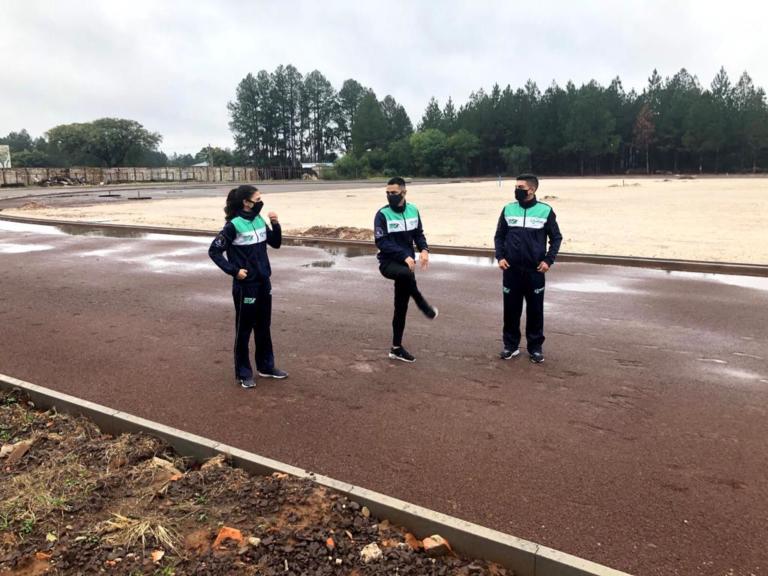 Foto horizontal de três atletas aquecendo, lado a lado, na pista de atletismo: uma mulher branca de cabelo longo preto e dois homens brancos de cabelo curto. Ao fundo, uma grande área arborizada.