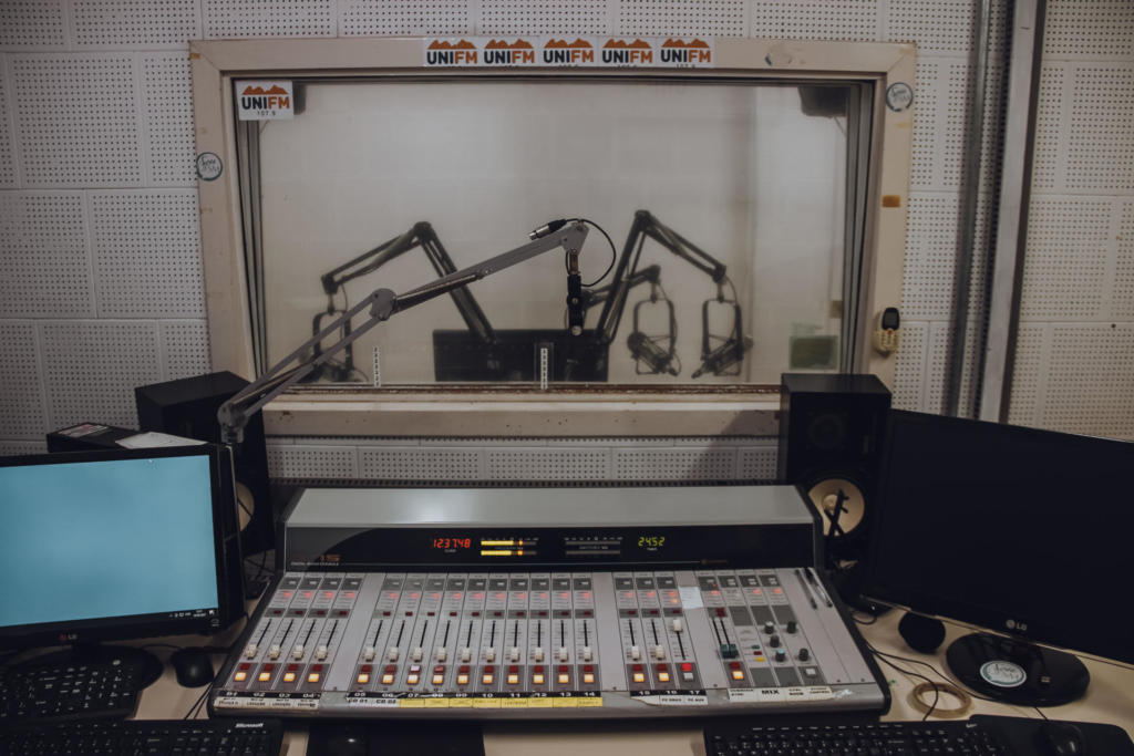 Foto horizontal colorida do setor técnico de um estúdio de rádio. Sobre uma bancada, há uma mesa de som entre dois monitores de computador. Ao centro, a mesa de som na cor cinza, com botões vermelhos e luzes amarelas, e um pequeno painel com números e detalhes sobre o som que está sendo transmitido da mesa para o rádio. O monitor à esquerda da mesa está ligado em uma tela de cor azul escuro. O monitor à direita da mesa está desligado. Junto aos monitores há equipamentos, como teclados, mouse e caixas de som. Ao fundo, há um vidro que mostra o estúdio da rádio, com as estruturas de suporte de microfone, onde são feitas as programações ao vivo.