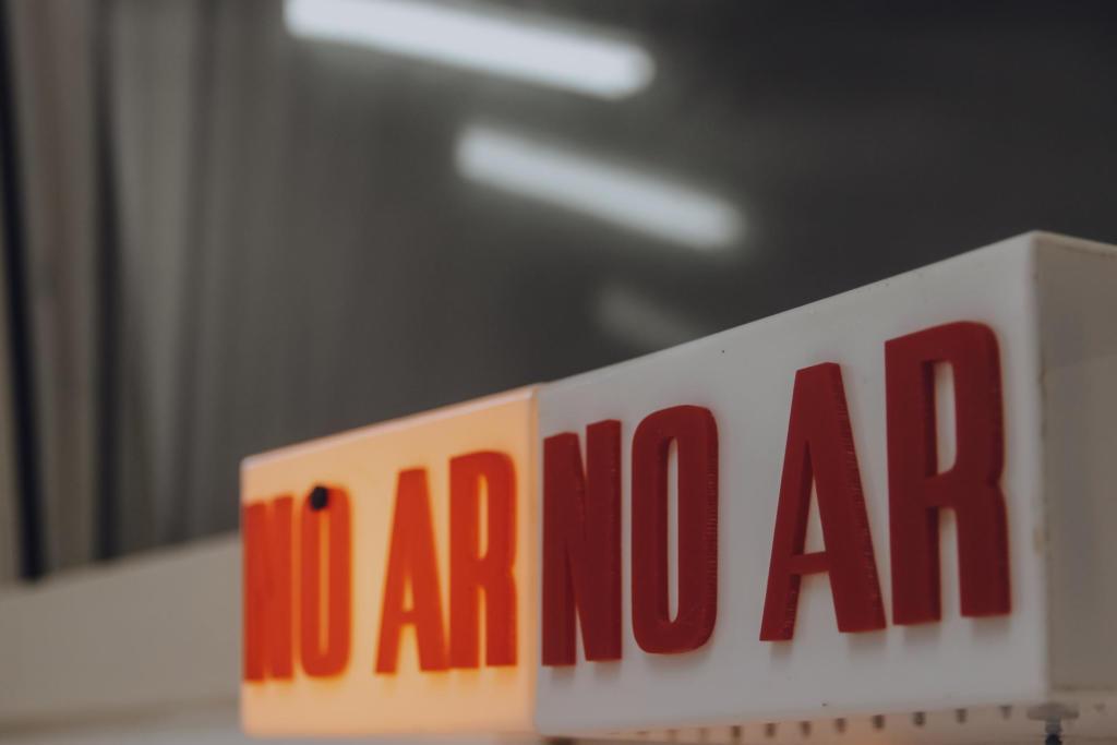 """Foto horizontal de dois letreiros, lado a lado, com a informação """"No Ar"""", dentro do estúdio da Rádio Universitária da Universidade Federal de Santa Maria. Os letreiros, em caixa alta e cor vermelha, estão inseridos em dois suportes em formato de paralelepípedo, na cor branca. Esses letreiros, quando iluminados, sinalizam que o programa de rádio está ao vivo naquele momento. O letreiro da esquerda, mais distante na imagem, está ligado, bem iluminado. O letreiro da direita, em foco na imagem, está desligado. Ao fundo da imagem, há o vidro que divide o estúdio e o setor onde a parte técnica da rádio fica."""